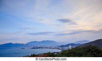 view of clouds at dawn over sea bay mountains and city on coast