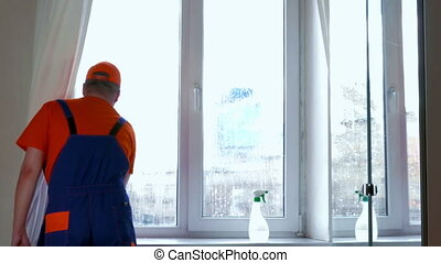 window cleaning - A man in overalls washes a window in...