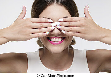 beauty woman smiling hiding her eyes with gel nails