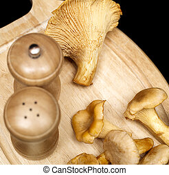 chanterelle mushrooms on the wooden cutting board against...