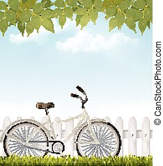 Bicycle in front of a white fence with green leaves.