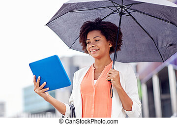 businesswoman with umbrella and tablet pc in city -...