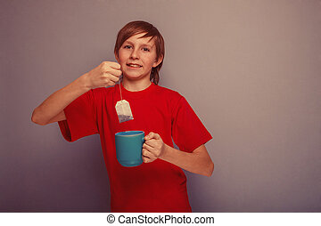 Boy, teenager, twelve years in the red shirt drinks tea bag...