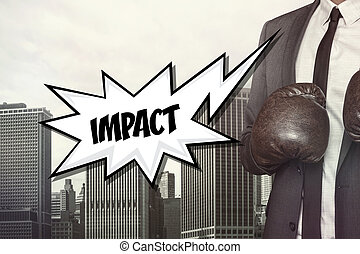 Impact text with businessman wearing boxing gloves on...