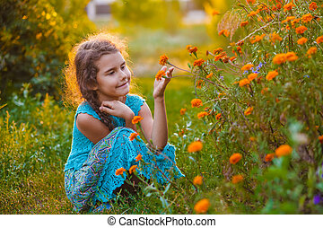 Girl sitting on his haunches and touching orange flower -...