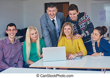 group of students getting suppport from teacher and working...