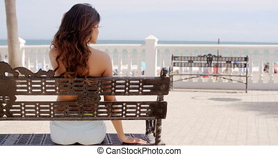 Happy young woman relaxing in the sun at the seaside sitting...