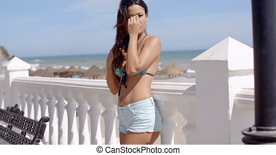 Sexy young woman in a trendy summer outfit standing sideways...