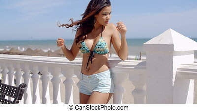 Gorgeous sexy woman on a seafront promenade standing...