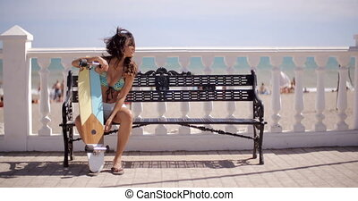 Sexy young woman resting on her skateboard - Sexy young...