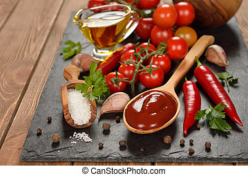 Tomato sauce and spices on a brown background