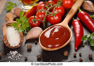 Tomato sauce and spices on a black background