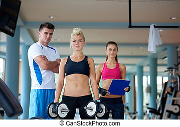 young woman in fitness gym lifting  weights