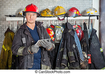Fireman Holding Digital Tablet At Fire Station - Portrait of...