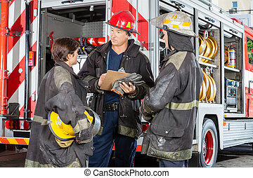 Firefighters Discussing Over Clipboard Against Truck - Male...