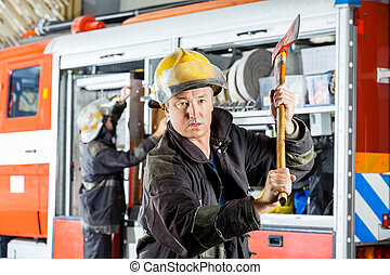Confident Fireman Holding Axe At Fire Station - Portrait of...