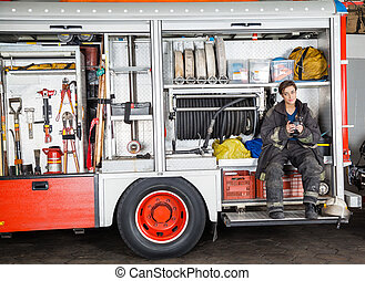 Firewoman Holding Coffee Mug In Truck - Full length of...