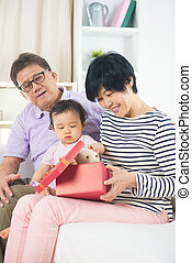 asian grand parents with grand daugther celebrating...