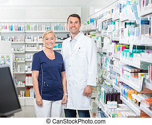 Confident Pharmacist And Assistant Standing In Pharmacy