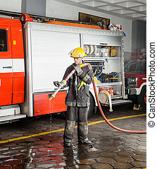 Fireman Holding Water Hose During Training - Full length of...