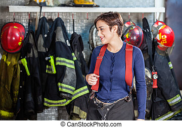 Firefighter Standing Against Uniforms At Fire Station -...