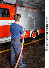 Fireman Spraying Water On Truck During Practice - Rear view...
