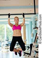 young woman in fitness gym lifting on bar