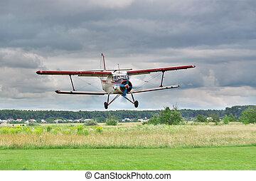 Biplane landing - Old biplane landing on grass airstrip with...