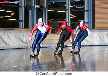 Three speed skaters making their laps on an indoor ice rink