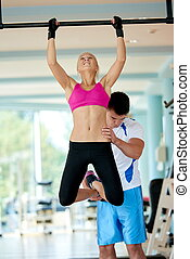 trainer support young woman while lifting on bar in fitness gym