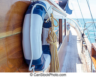 Lifebuoy on the wall of sailboat with rope.