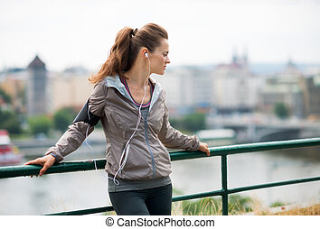Woman runner with headphones in profile, up against...