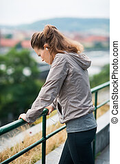 Woman runner in profile, leaning against guardrail, looking...