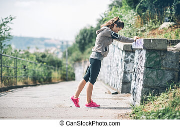 Woman runner stretching against rock wall - Feel that burn,...