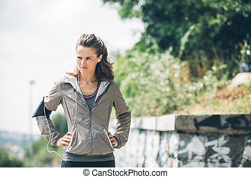 Woman runner with hands on hips looking off into distance -...