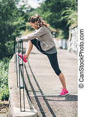 An athletic woman in profile stretching out against...