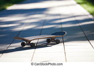 Old used skateboard on street - Old used skateboard isolated...