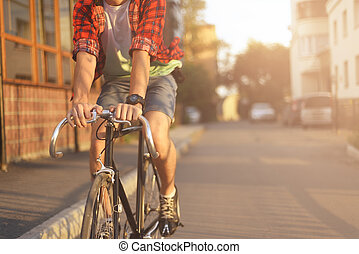 Close up hipster on bike in the city at sunset. Shot with...