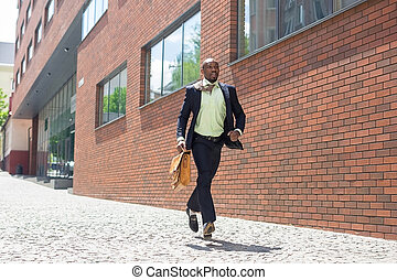 african black young businessman running in a city street -...