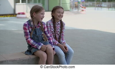Joyful Talk in Schoolyard - Two cheerful school girls...