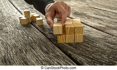 Closeup of businessman assembling blank wooden cubes into a...