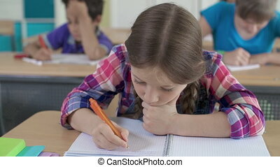 Studying Hard - Tired pupil writing in her notebook during...
