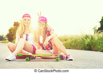 Attractive smiling hipster teenage friends with skateboard,...