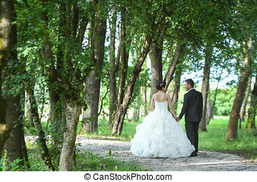 Bride and groom walking in nature - A rear view of the bride...