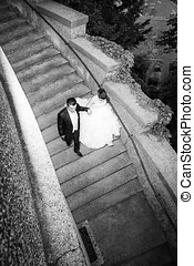 Newlyweds walking down stone steps bw - A high angle view of...