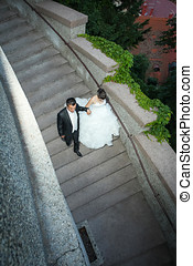 Newlyweds walking down stone steps - A high angle view of...