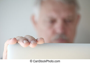 Senior man with hand on laptop cover - Older man has hand on...