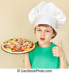 Little smiling kid in chefs hat with cooked appetizing pizza...