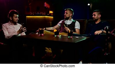 Group Boys smoking hookah in the lounge caffee - Group of...