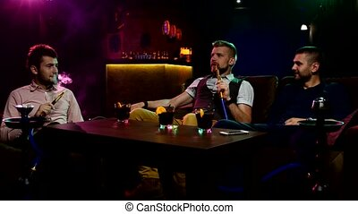Boys smoking hookah in the lounge caffee - Group of young...